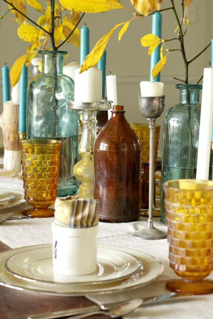 Mixed Metals Candlesticks and Vintage Bottles in Centerpiece