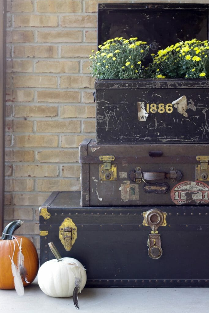 Trio of vintage trunks with mums and pumpkins on fall porch