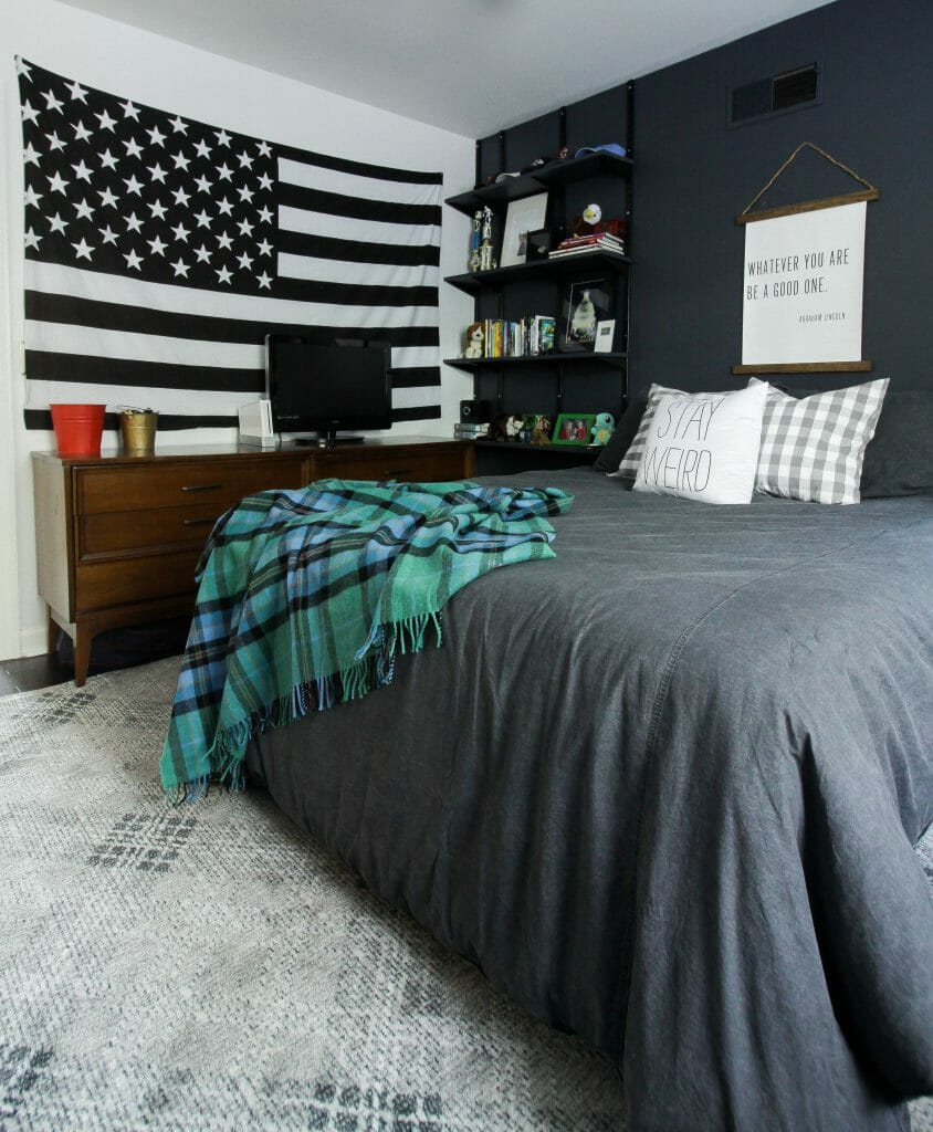moody teen boy bedroom with touches of plaid and budget track shelving