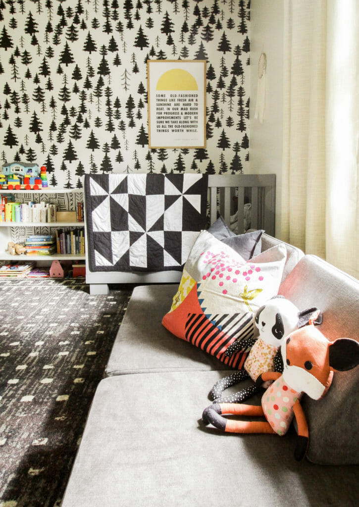 adorable nursery with black and white tree wallpaper