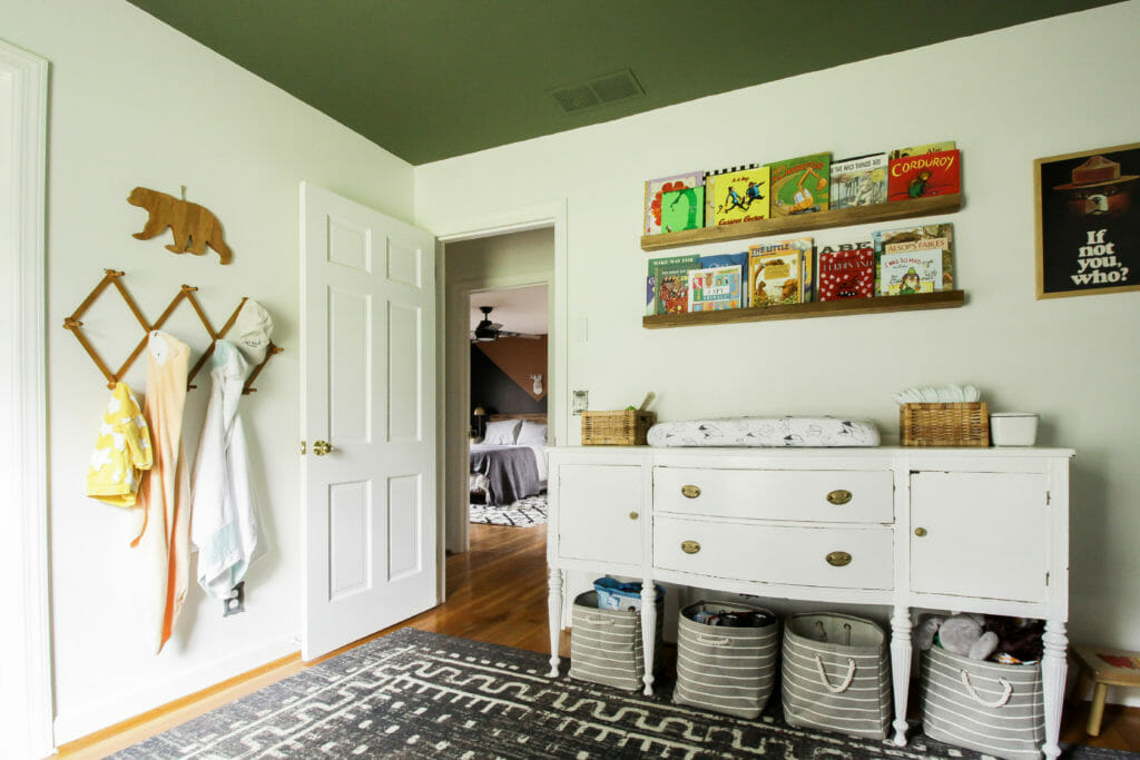 painted green ceiling in nursery with vintage sideboard as changing table