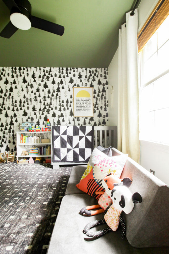 Nursery with green painted ceiling and grays and blacks and tree wallpaper