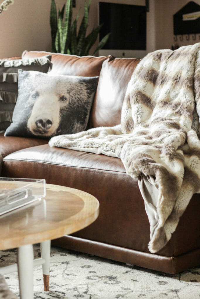 bear pillow on leather sofa and fur throw