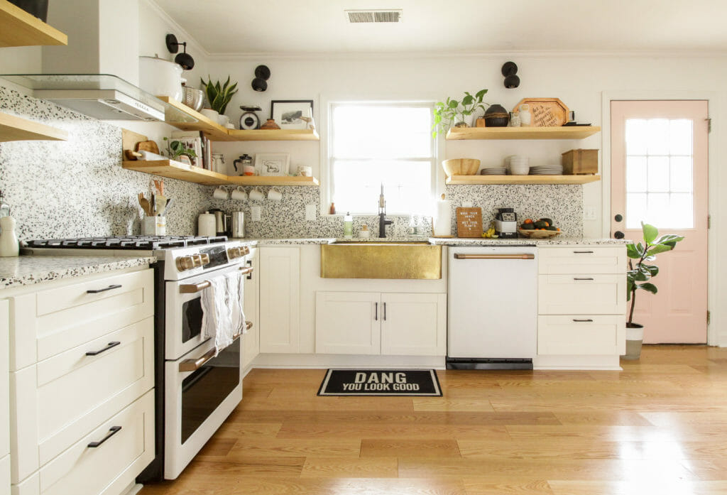 Eclectic kitchen in white, gold, black with pink door.