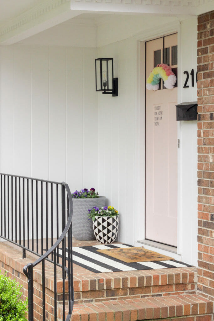 small front porch with pink door and planters