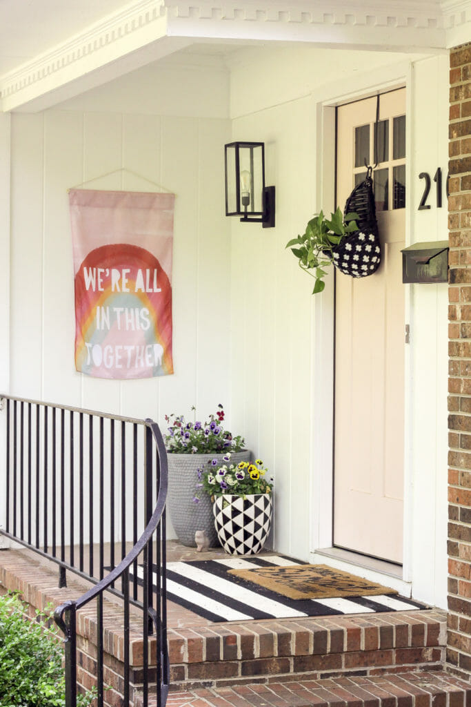 Cheerful Spring Porch with rainbow flag and pink door and black and white planter and mat