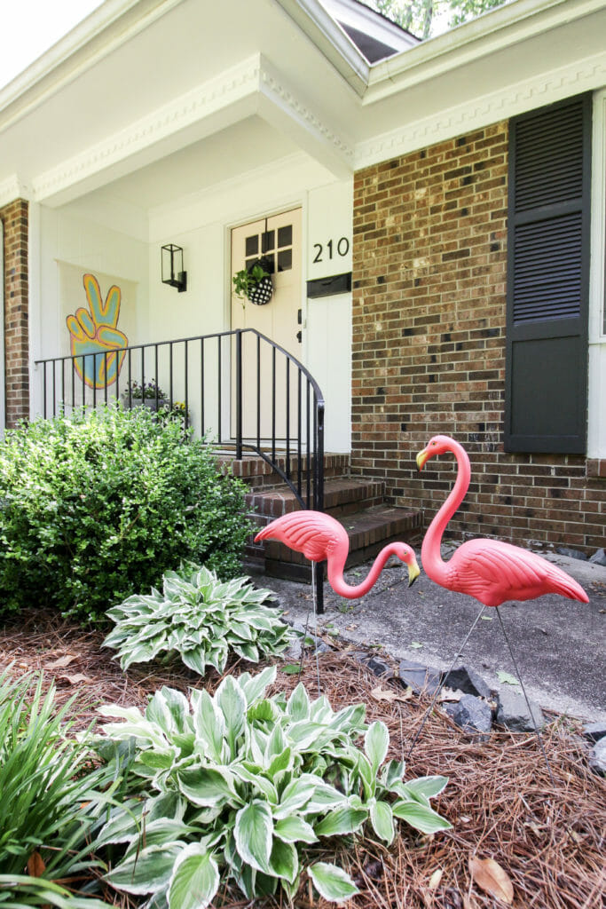 pink, black, white front porch with vintage flamingos