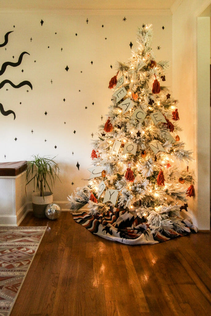 flocked tree with DIy ornaments in warm colors
