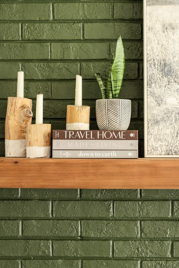 minimal mantel styling books and candle holders and plant